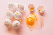 Top View Of Broken Glittered Egg With Text Happy Easter And Raw Eggs In Plastic Box On Pink Background
