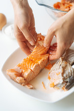 Crop Hands Of Female Separating Piece Of Cooked Salmon From Bones While Preparing Dinner At Home