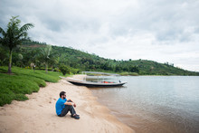 Caucasian Male Tourist Sitting On Lake Kivu Shore Observing The Water With Green Lush Vegetation In The Background
