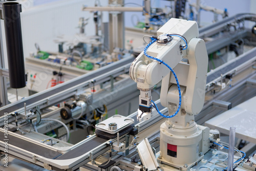 Fototapeta Industry 4.0 concept; artificial intelligence in smart factory prototype. Robot arm picks up the product from automated car on production line. Focus on automated car. Selective focus. obraz na płótnie