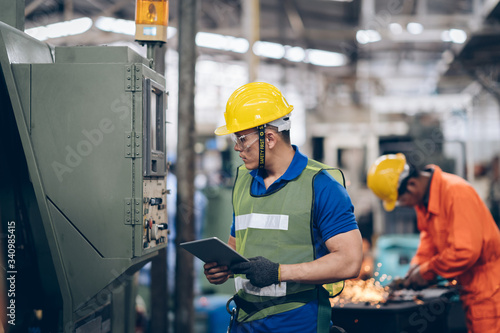 Fotomural technician engineer checking process on tablet to machinery in factory