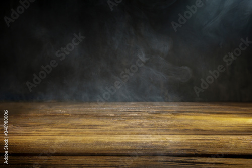 Photo An old wooden table on a black background with smoke