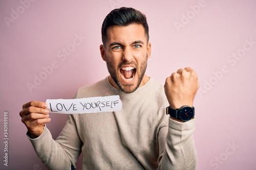 Valokuva Young handsome man holding paper with self love message over pink background ann