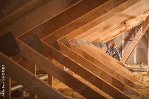 Fototapeta Construction Worker Insulating Attic Space Of Home.