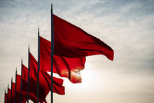 Low Angle View Of Red Flags Waving In Row Against Sky During Sunset