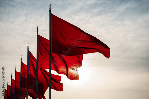 Low Angle View Of Red Flags Waving In Row Against Sky During Sunset - fototapety na wymiar