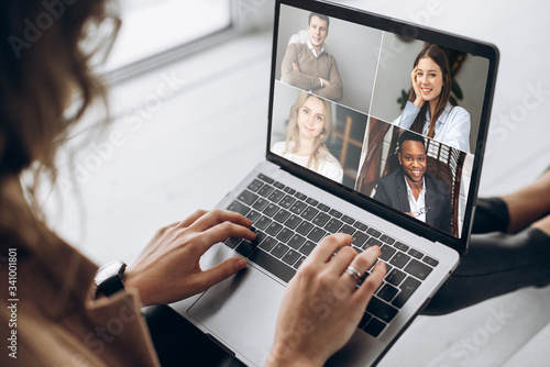 Fototapeta Online business meeting. Business team working from home in a video conference. .The girl communicates via video call communication using laptop with her business colleagues about the future strategy obraz na płótnie