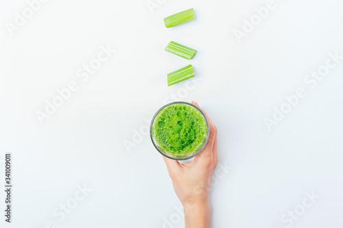 Fotografie, Obraz Female hand holds glass of green smoothie drink