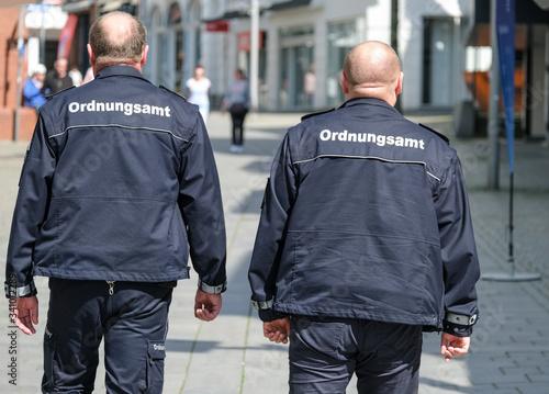 Foto Konzept Ordnung und Sicherheit: Zwei Mitarbeiter des Ordnungsamtes in Uniform au