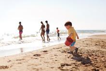 Cute Boy Walking On Shore With Bucket