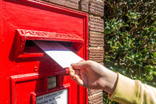 A Child's Hand Posting A Letter Into A Post Box Embedded Into A Brick Pillar.