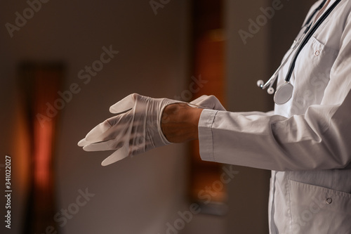 Profile photo, close-up: the doctor puts on sterile disposable latex gloves Canvas Print