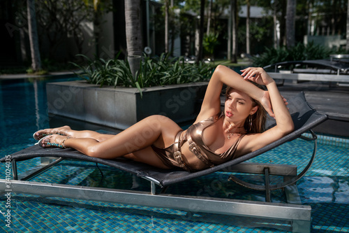 Obraz Sexy lady with perfect athletic body in a trendy gold bikini relaxes on a sun lounger near the pool - fototapety do salonu