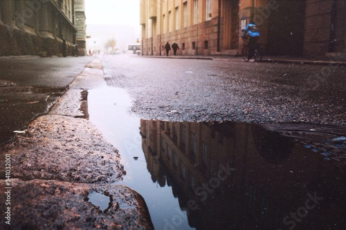 Photo Reflection Of Building In Puddle On Street