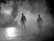 Full Length Of Silhouette Man And Woman Walking On Smoke Covered Street At Night