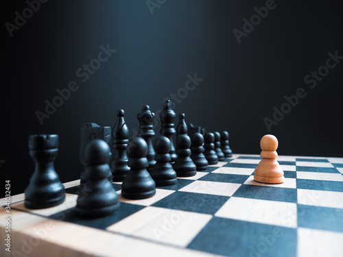 Fotografie, Obraz A single white chess pawn piece standing alone on a chessboard against a full team