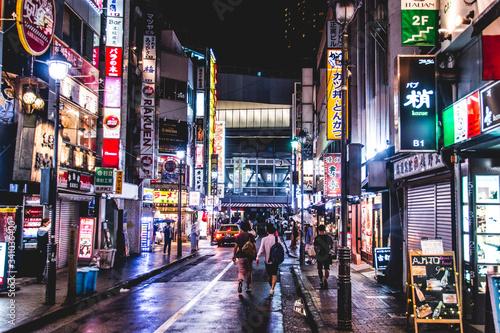 Obraz People Walking On Illuminated City Street Amidst Building At Night - fototapety do salonu
