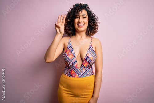 Young beautiful arab woman on vacation wearing swimsuit and sunglasses over pink background showing and pointing up with fingers number three while smiling confident and happy Canvas Print
