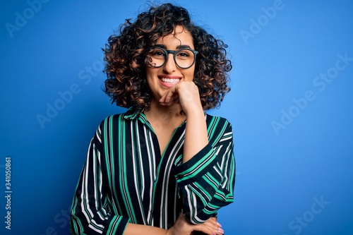 Photo Young beautiful curly arab woman wearing striped shirt and glasses over blue background looking confident at the camera with smile with crossed arms and hand raised on chin