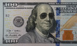 Happy smiling president Franklin portrait wearing sunglasses on 100 dollar bill. Concept of economic growth