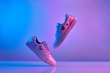 Trendy White Teenage Sneakers Flying In Trendy Neon Light. Levitation Shoes In Red, Blue Light. Creative Minimalism.