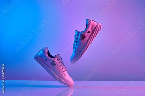 Fotografia Trendy white teenage sneakers flying in trendy neon light