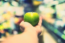 Close-up Of Hand Holding Apple Against Blurred Background