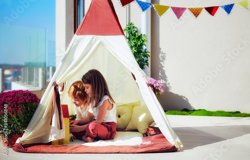 Fotografia cheerful kids are playing in teepee tent on a sunny patio
