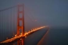 Illuminated Golden Gate Bridge Over River In Foggy Weather At Dusk