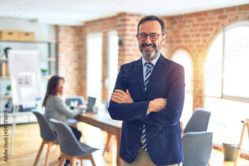 Fotografija Middle age handsome businessman wearing glasses   standing at the office happy face smiling with crossed arms looking at the camera