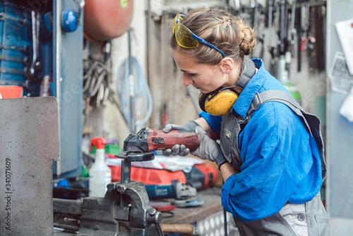 Fotografie, Tablou Woman mechanic working with disk grinder