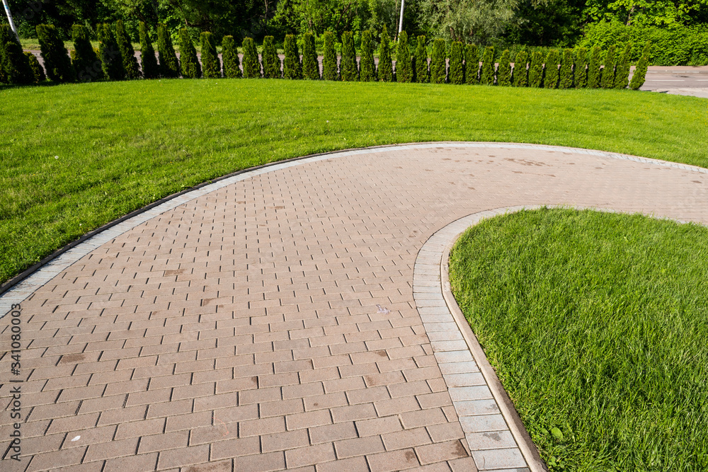 Fototapeta curved stone walkway from pavers in landscape design and sidewalk decoration