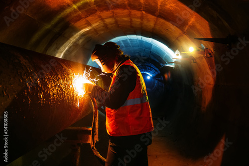 Valokuvatapetti Worker in protective mask welding pipe in tunnel