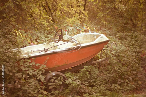 Photo Abandoned Motorboat On Plants Covered Field