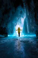 a girl in a yellow jacket stands at the exit of an ice cave in bright light