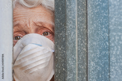 Photo A frightened grandmother in a mask peeps out of the gap in the fence through the gate of her house