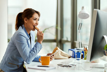 Smiling Businesswoman Eating A...