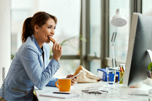 Canvas Print Smiling businesswoman eating a cookie while using mobile phone in the office
