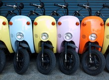 Colorful Motor Scooters Parked In Row On Footpath