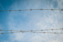 Low Angle View Of Barbed Wires Against Blue Sky