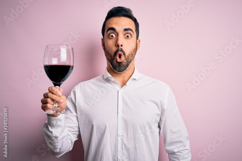 Photo Young handsome man with beard drinking glass of red wine over isolated pink back
