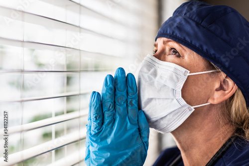 Vászonkép Prayerful Stressed Female Doctor or Nurse On Break At Window Wearing Medical Fac