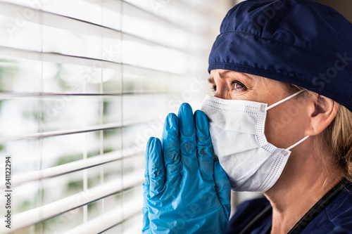 Prayerful Stressed Female Doctor or Nurse On Break At Window Wearing Medical Fac Fototapeta