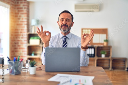Fototapeta Middle age handsome businessman wearing tie sitting using laptop at the office relax and smiling with eyes closed doing meditation gesture with fingers. Yoga concept. obraz