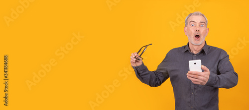 Photo amazed adult or senior man with book isolated on color background