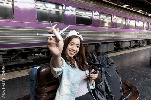 Papel de parede Happy young Asian lady tourist with model airplane at train station