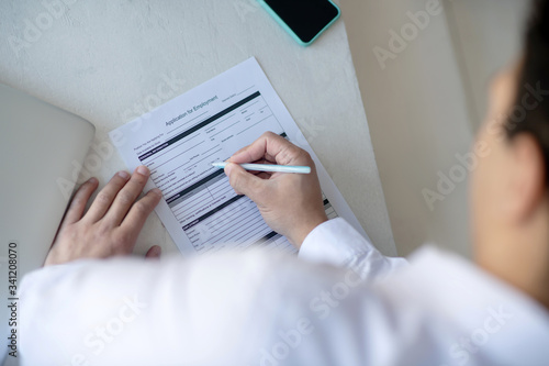 Fotografie, Tablou Dark-haired man in a white shirt signing the unemployment application