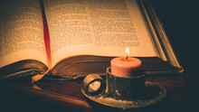 Close-up Of Lit Candle And Bible On Table In Darkroom