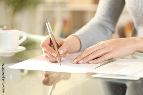 Woman hands writing a letter on a desk at home Billede på lærred