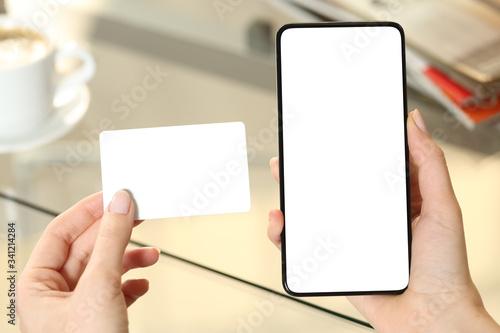 Obraz Woman hands holding credit card and blank phone screen - fototapety do salonu